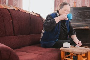 Senior lady - elderly woman at home drinking from a mug - pension life