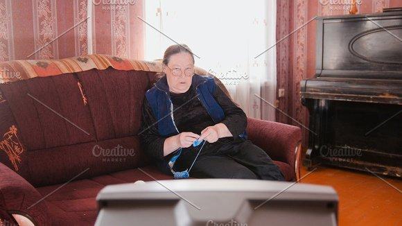 Old lady home at sofa - senior woman watching television and knits wool socks