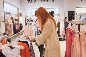 Beauty woman in a clothing store chose a dress - shopping concept