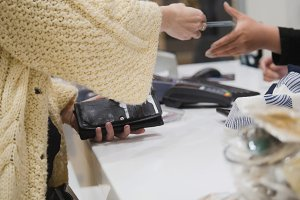 Woman paying by credit card in dress store - trading concept