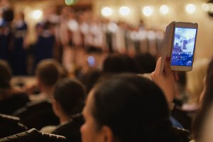 Audience in concert hall during performing piano girl- people shooting performance on smartphone, music opera