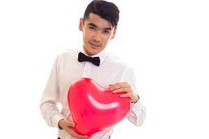 Young man with bow-tie holding balloon