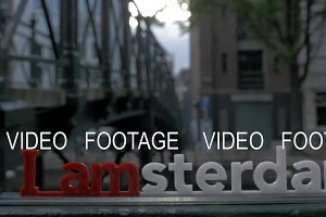 View of small plastic figure of Iamsterdam letters sculpture on the bridge against blurred cityscape, Amsterdam, Netherlands