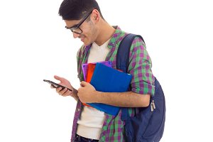 Young man with backpack, smartphone and books