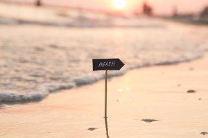 Summer holidays idea - beach sign and sunset