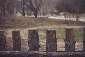 Spaced wood fence with gaps in outdoor scene - with copyspace