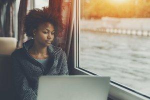 Ebony girl with laptop on ship