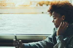Curly mixed girl with phone on ship
