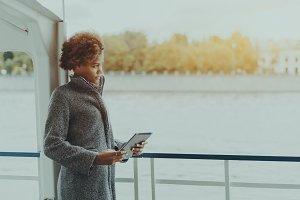 Girl with digital pad on ship deck
