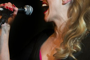 Blond woman singing with microphone
