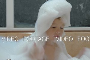Child having fun with foam in the bath