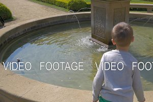 view of small boy throwing coins into the water, Prague, Czech Republic