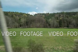 Timelapse view from riding train window of coutryside landscape, trees, forests, houses against cloudy sky