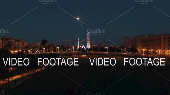 Aerial Night View Of Lighted Ferris Wheel And Bridge Against Sky With Moon Valencia Spain