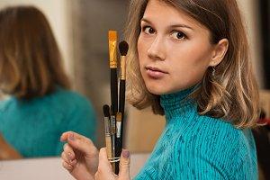 Girl holding brushes