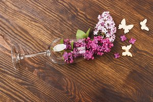 Wineglass with lilacs and butterflies