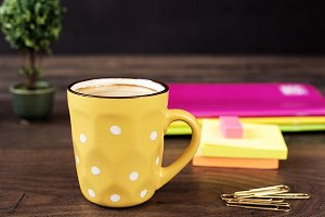 Yellow cup of coffee with white dots