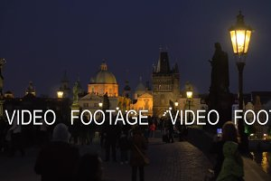 Evening cityscape with walking people on the picturesque Charles Bridge, Prague, Czech Republic