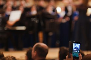 Spectators at concert - people shooting performance on smartphone, music opera