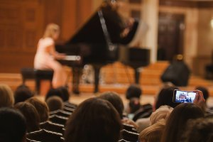 Spectators in concert hall during performing piano girl- people shooting performance on smartphone