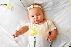 little baby girl with daffodils. 5month baby. Flowers in baby hands. First spring blossoms.Little girl in white