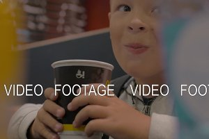 View of small boy drinking from the paper cup and smiling, fast food cafe