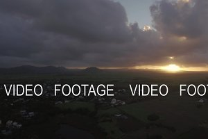 Aerial view of Mauritius Island, forests, farm, fields and hills against sunset sky and pink clouds