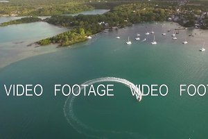 Flying over motor boat sailing in bay, Mauritius Island