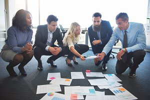 Business team comparing ideas in office