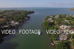Mauritius coastal town and river falling into ocean, aerial view
