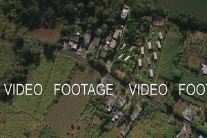 Aerial top view of countryside district, agricultural fields, streets, roofs of houses, forest