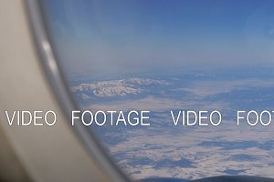 Aircraft wing and picturesque mountain landscape from high level from airplane window