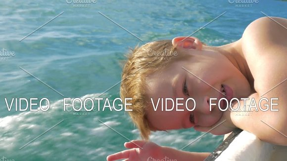 Child traveling by boat and trying to touch water