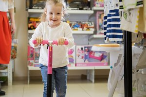 Happy little girl plays with bicycle in kids store