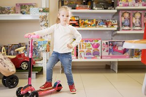 Happy blonde little girl playing with bicycle in kids store