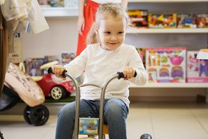 Portrait of little girl playing with kids bicycle in children's store