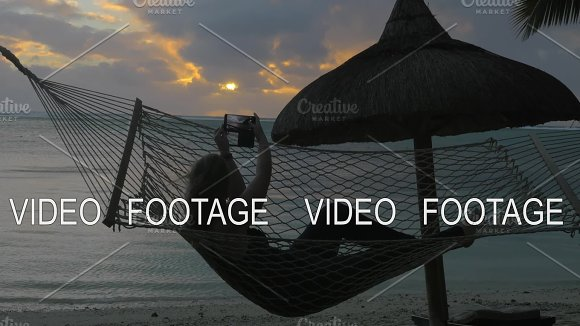 Woman Relaxing In Hammock On Beach And Taking Cell Photos