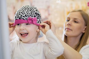 Little happy girl with mommy doing shopping and buying pink hat in kids dress store
