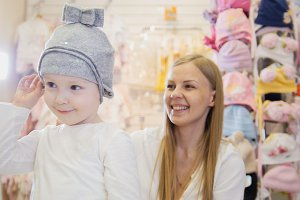 Kids dress store - little blonde baby girl with mother doing shopping and buying hat