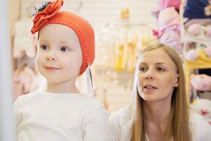 Kids dress store - little blonde baby girl with mother doing shopping and buying red hat