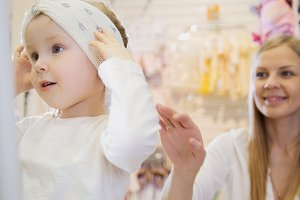Baby's dress store - little blonde baby girl with mother doing shopping and buying pretty hat