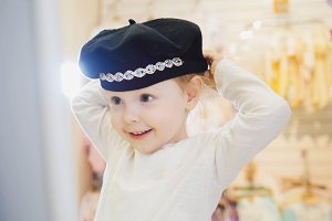 Child's dress store - little blonde baby girl doing shopping and buying pretty hat