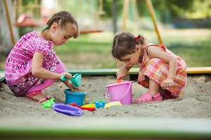 Two girls play in the sandbox