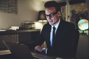 Smiling businessman working on laptop at night
