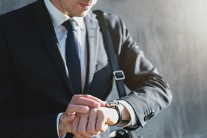A businessman setting time on the watch