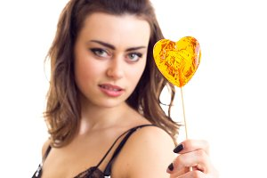 Young woman in black bra with candy