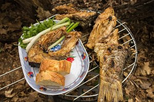 Cooked fish on the barbecue.Bread, fish, greens.