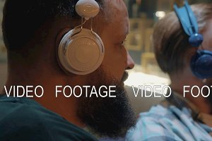 Close up view of two bearded men listening musics using colorful on-ear headset
