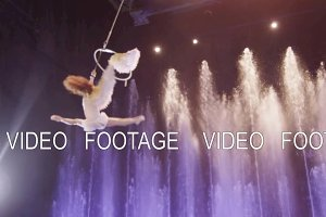 Aerial performer making acrobatic act against colorful fountains, acrobatics, Moscow, Russia
