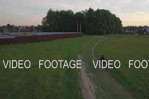 Aerial steadicam view of boy riding a bike at summer, Russia
